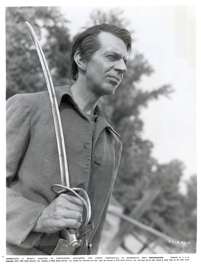 """Raymond Massey, in a scene from the movie, """"Abe Lincoln in Illinois"""". He is shown as Lincoln holding a sword outside. 