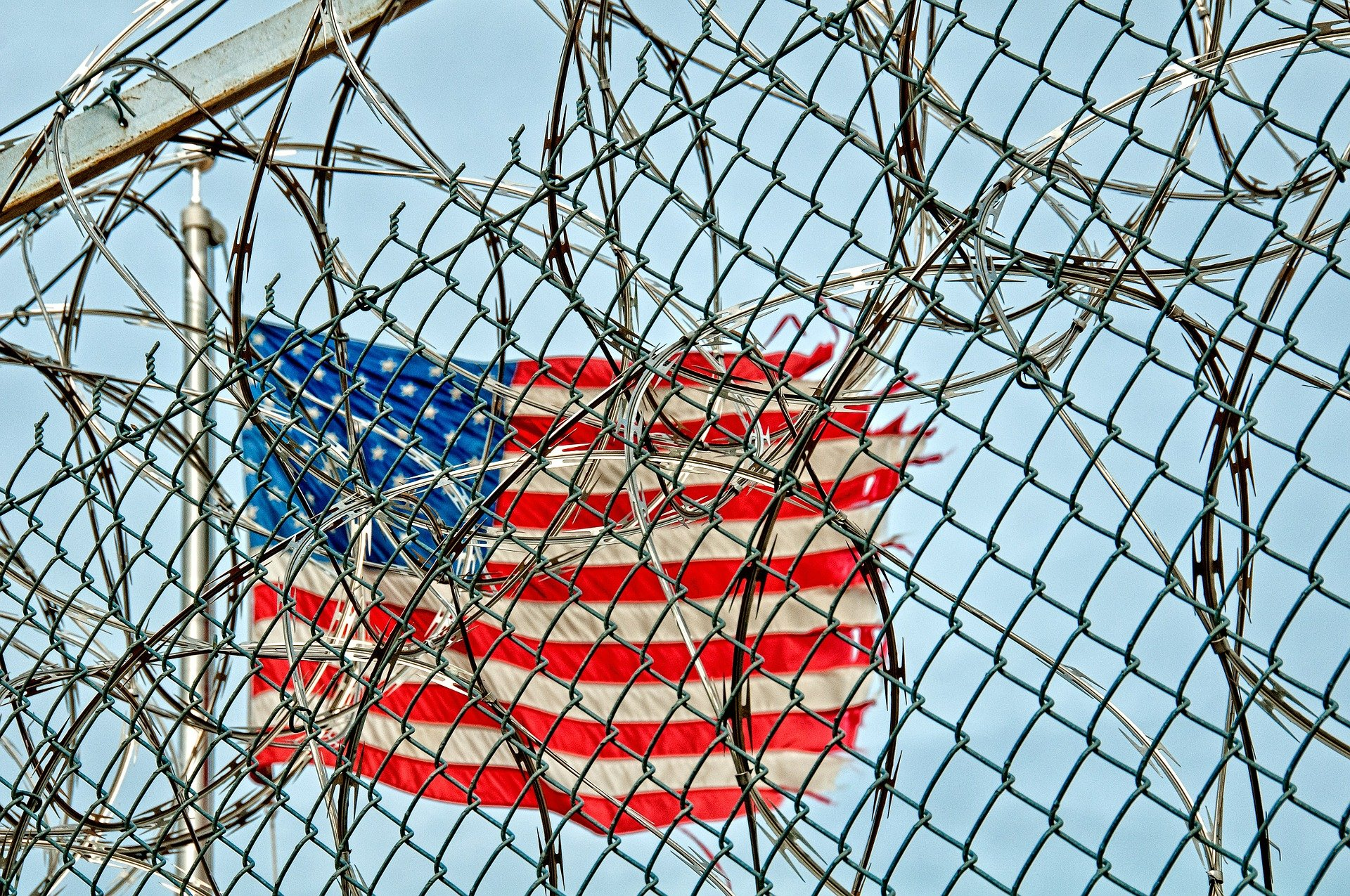 Pictured - Prison detention wire fence and the American flag | Source: Pixabay