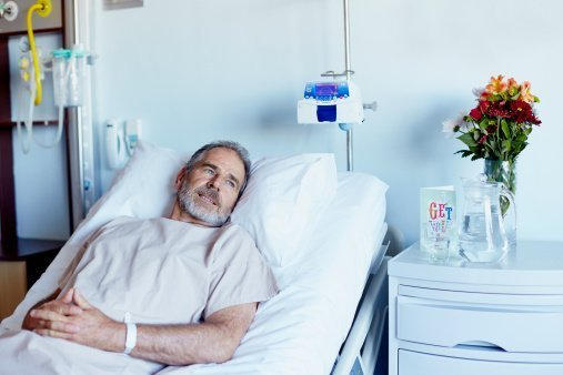 Man relaxing on bed in hospital ward | Photo: Getty Images