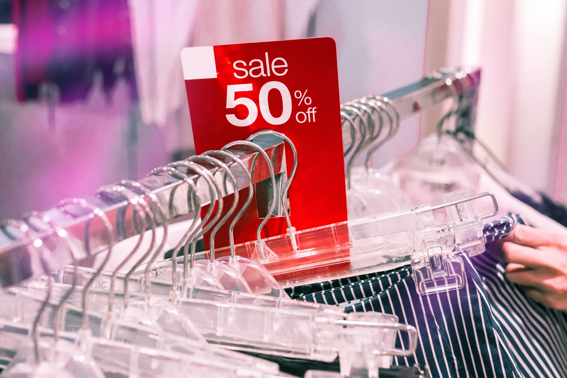 Clothing rack with a sale sign | Source: Pexels