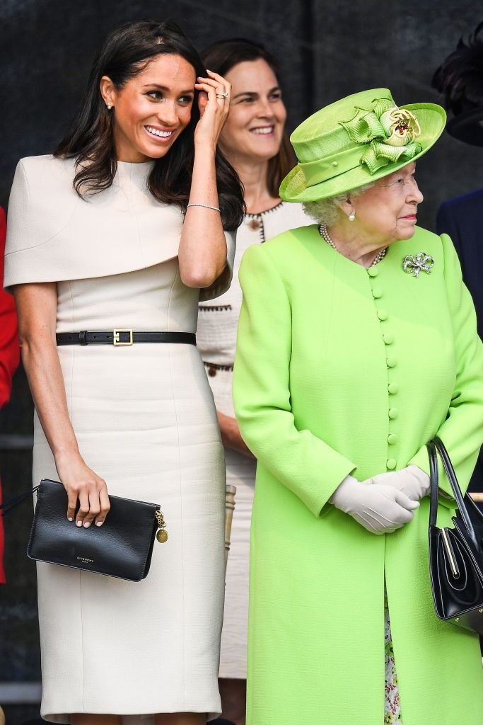 Queen Elizabeth II stands with Meghan, Duchess of Sussex accompanied by Samantha Cohen during a ceremony to open the new Mersey Gateway Bridge | Getty Images