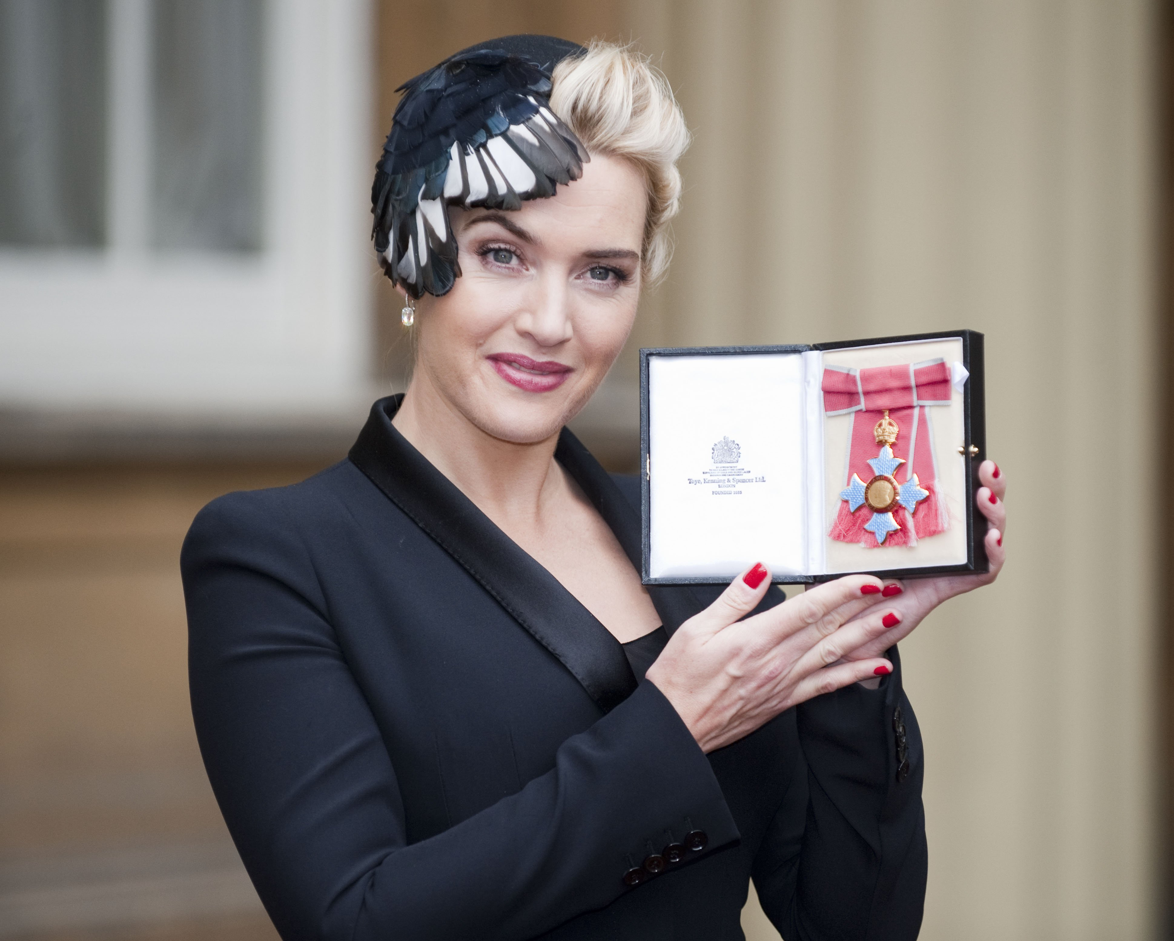 Kate Winslet holds her CBE, which was awarded to her by Queen Elizabeth II during an Investiture ceremony at Buckingham Palace on November 21, 2012. | Photo: Getty Images