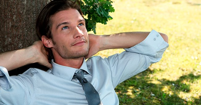 A photo of a man relaxing against a tree. | Photo: Shutterstock