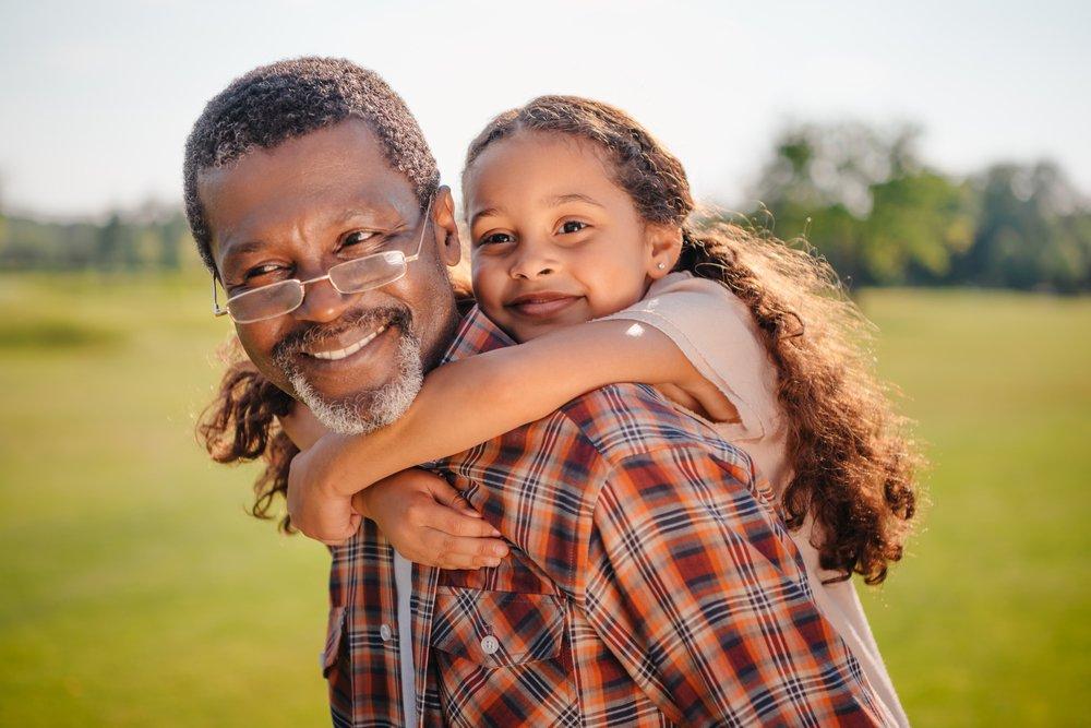 Nieta feliz abraza a su abuelo sonriente en el césped verde. | Fuente: Shutterstock