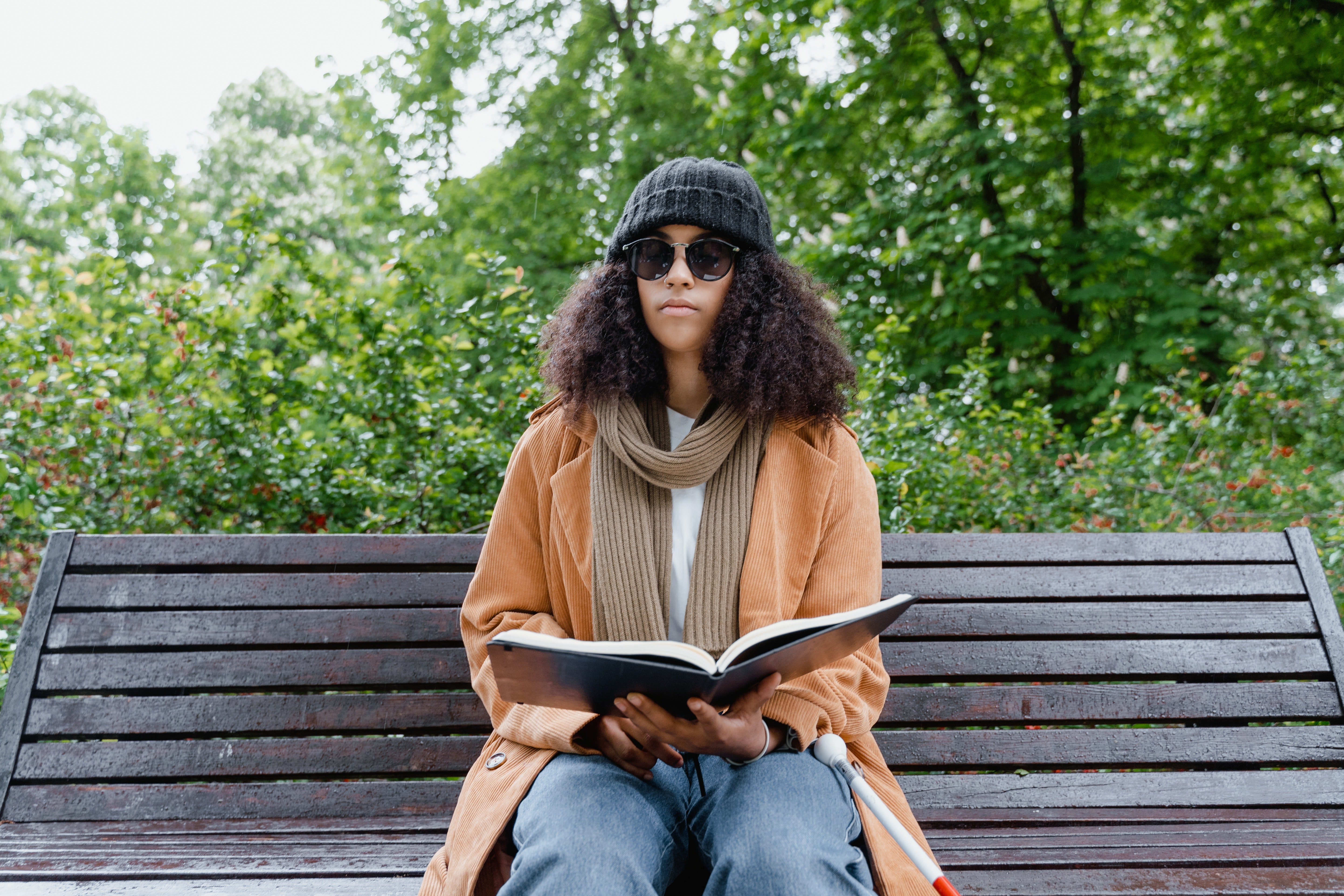 Pictured - A young woman sitting on a bench holding a book wearing sunglasses | Source: Pexels