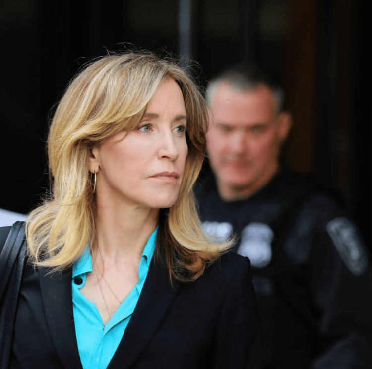 For her role in the college admissions scandal, Felicity Huffman is escorted by police and legal team she leaves the John Joseph Moakley United States Courthouse, on April 3, 2019, Boston | Source: Pat Greenhouse/The Boston Globe via Getty Images