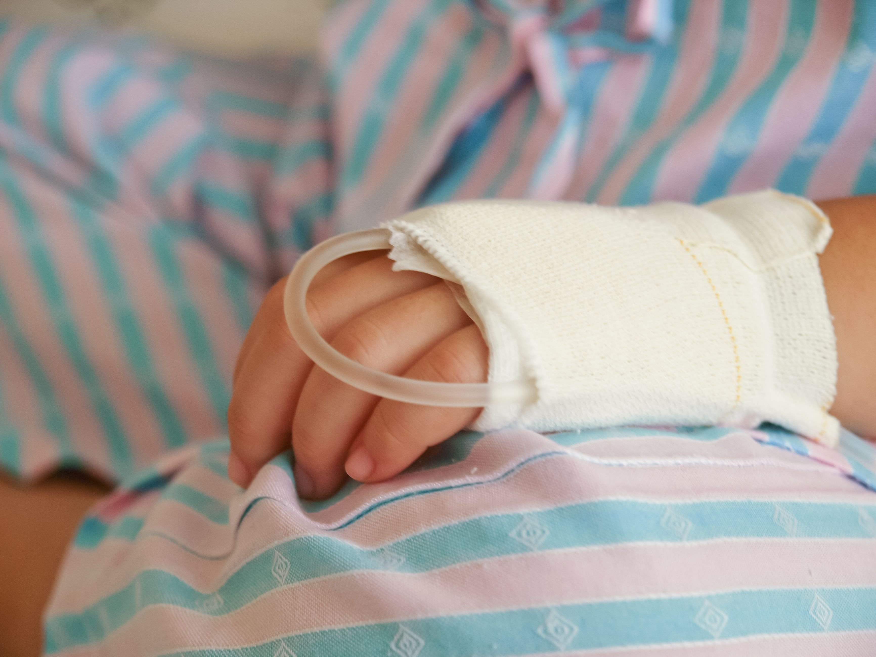 A sick child in the hospital with a dextrose on the hand. | Source: Shutterstock