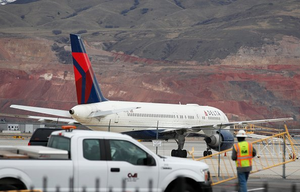 A worker sets up barriers as a Delta plane sits idle at the Salt Lake International Airport after it was closed due to an earthquake on March 18, 2020 in Salt Lake City, Utah | Photo: Getty Images
