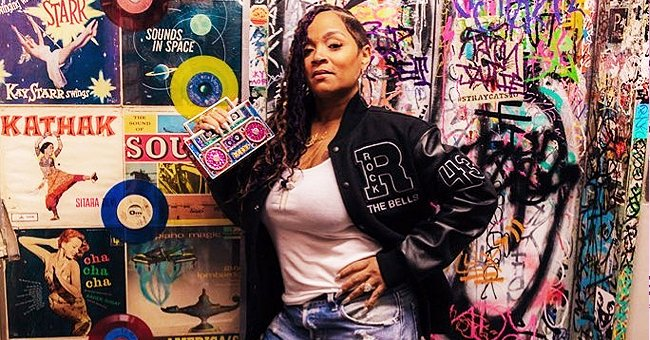LL Cool J's Wife Simone Smith Poses with Boombox Accessory in Front of a Vinyl Record Wall Display