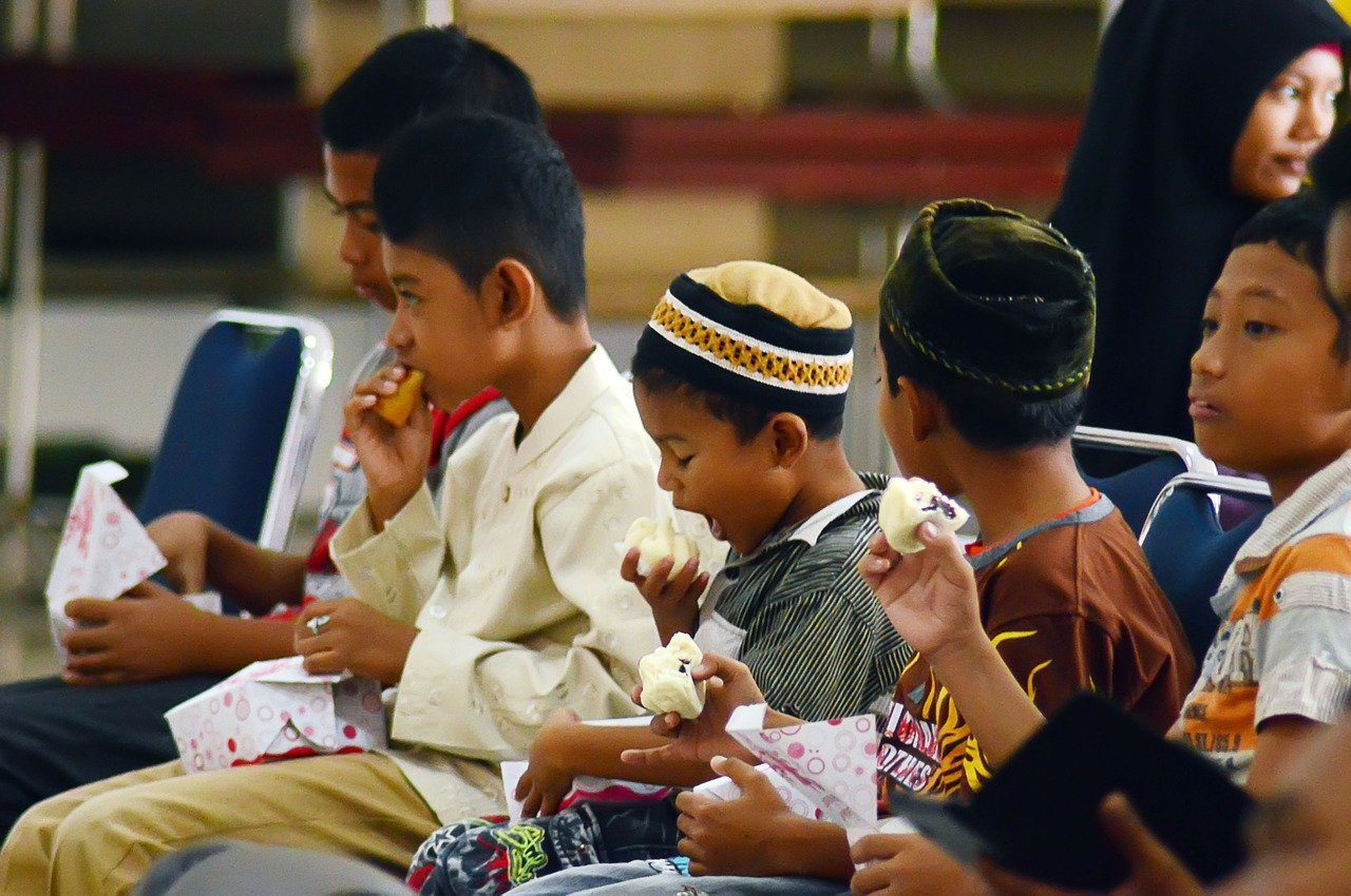 A group of different aged children eating lunch together   Photo: Pixabay/Saiful Mulia