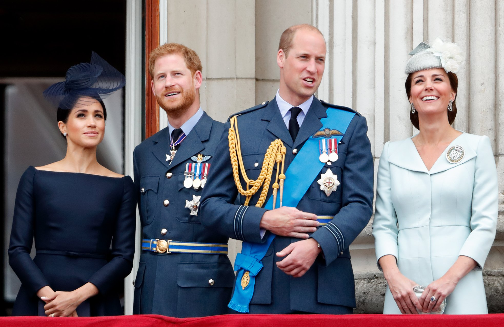 Meghan Markl, Prince Harry, Prince William and Kate Middleton smile while looking up from the balcony at the Buckingham Palace | Photo: Getty Images