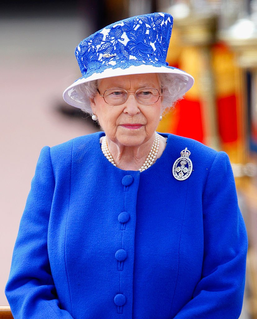 La reine Elizabeth II se tient sur une estrade à l'extérieur du palais de Buckingham lors de la cérémonie annuelle Trooping the Colour, le 15 juin 2013, à Londres, en Angleterre. | Photo : Getty Images
