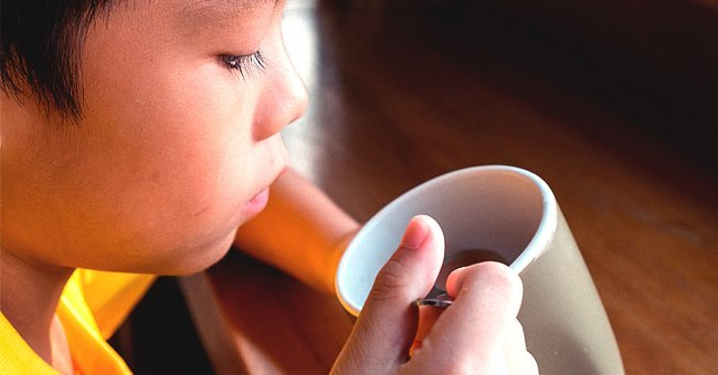 A young boy sipping from a cup of coffee | Photo: Shutterstock