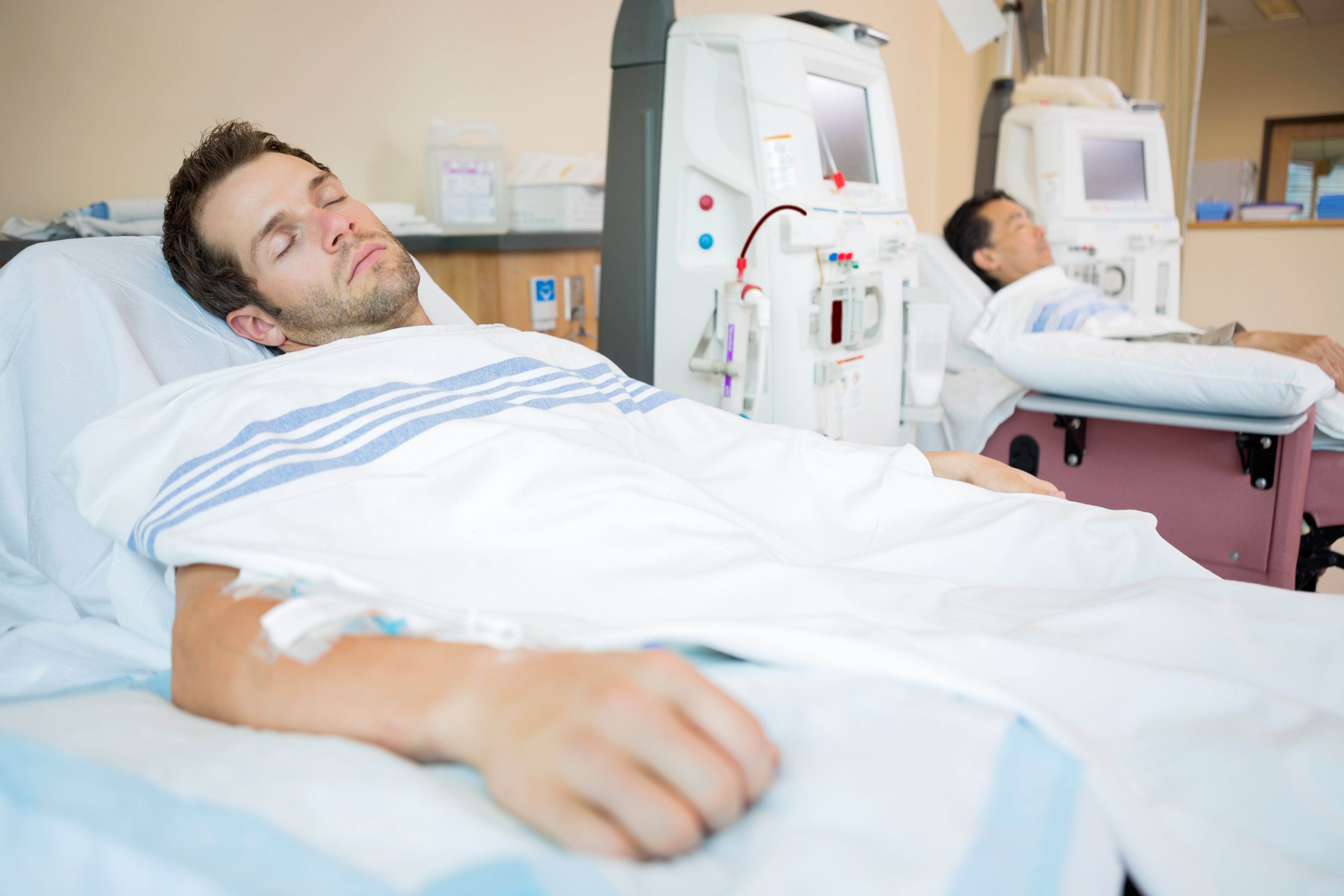 Male patients sleeping while receiving renal dialysis in chemo room at hospital | Photo: Shutterstock.com
