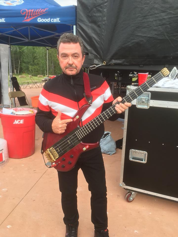 Tony Lewis posing with his bass guitar in 2018.   Source: Wikimedia Commons.