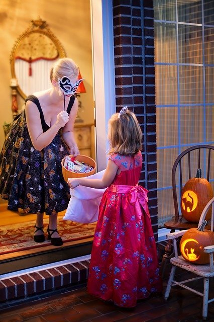 Young girl is trick-or-treating with woman who has face masks and treats | Photo: Pixabay