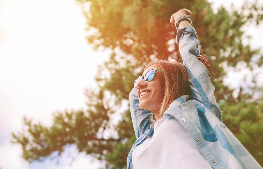 Mujer feliz con lentes de sol al aire libre. Fuente: Shutterstock