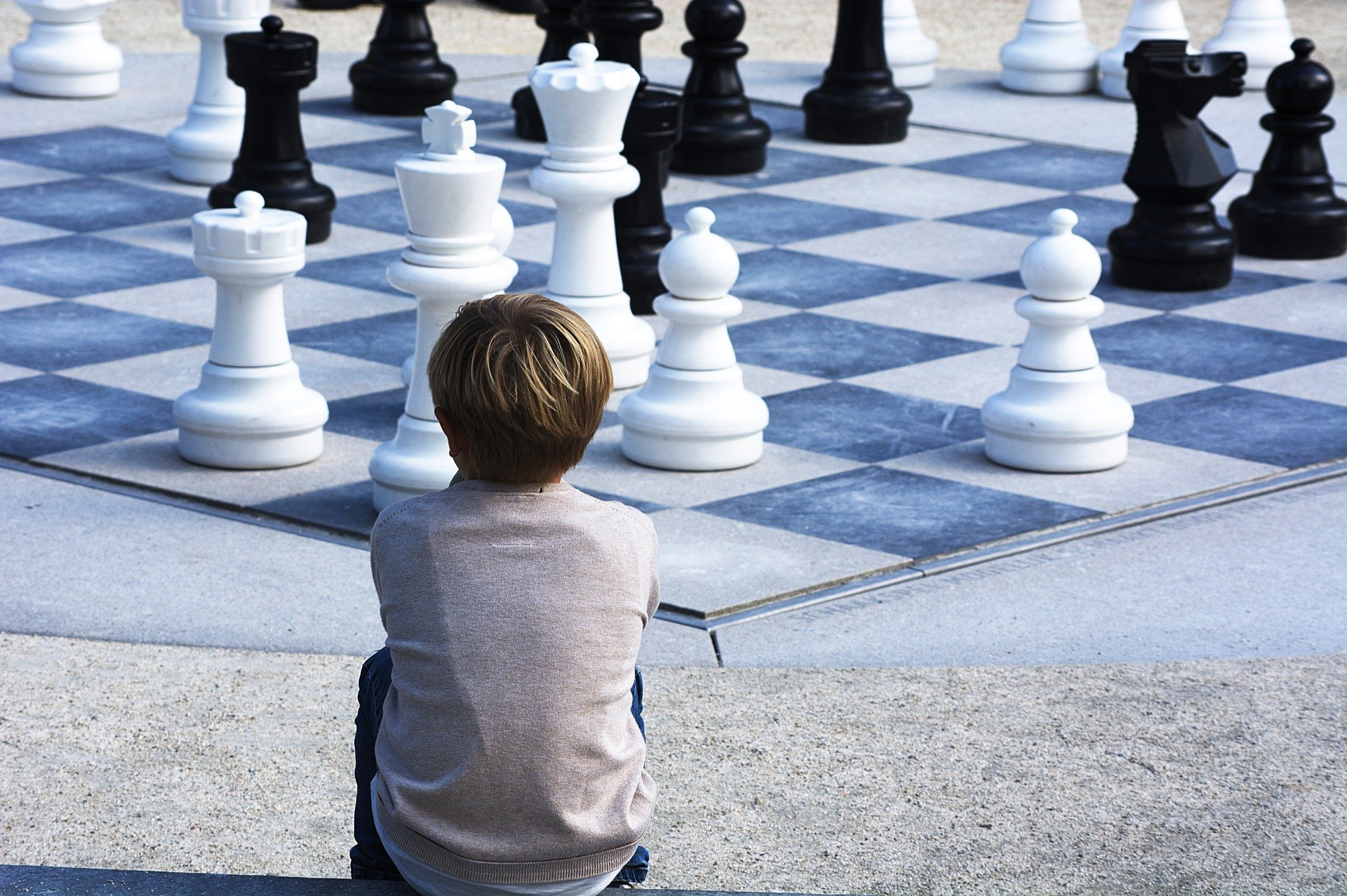 Pictured - A young boy sits and looks over at a chess landscape   Source: Pixabay