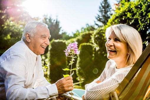 Photo of a happy senior man presenting flower to his wife in a garden | Photo: Getty Images