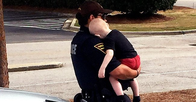 A police officer consoles a 1-year-old baby abandoned by his parents following heroin overdose.   Photo: facebook.com/Fayetteville.Police