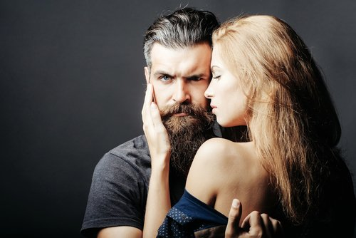 A young bearded man held by a young blond woman. | Source: Shutterstock.