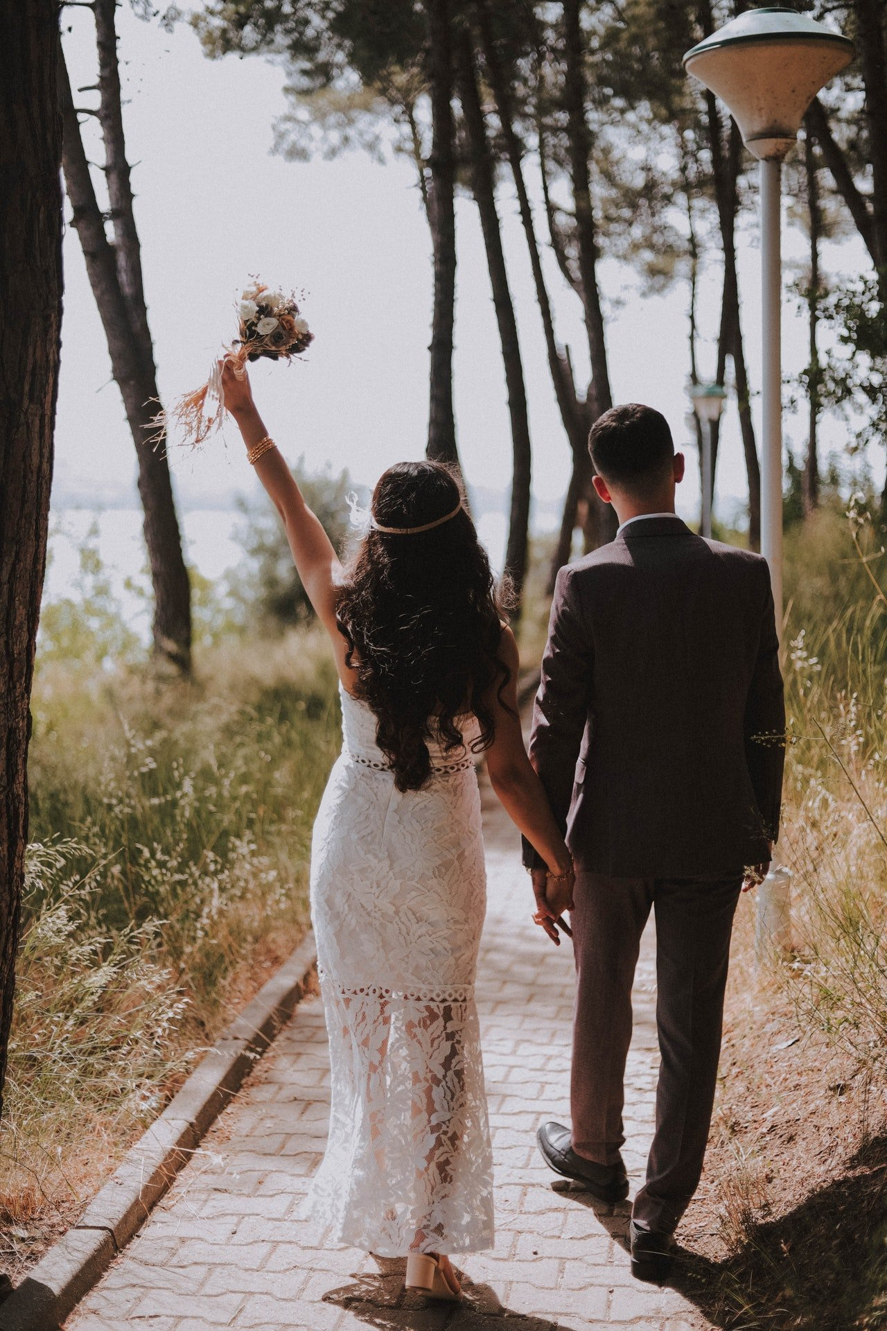 A couple walking in the woods in their wedding outfits.   Photo: Pexels