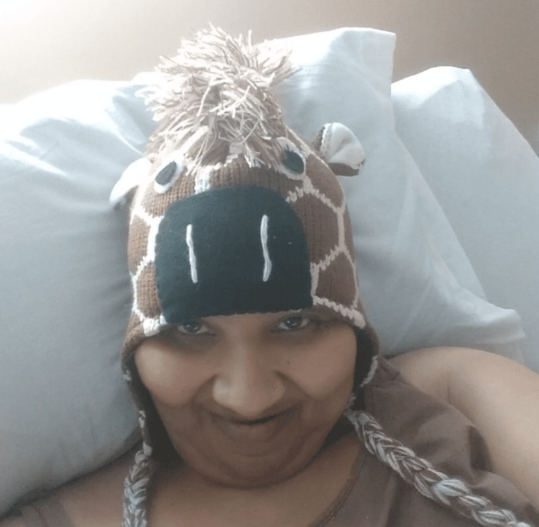 Pictured - A photo of Renee Biran smiling while on the bed | Source: Facebook/@reneebiran