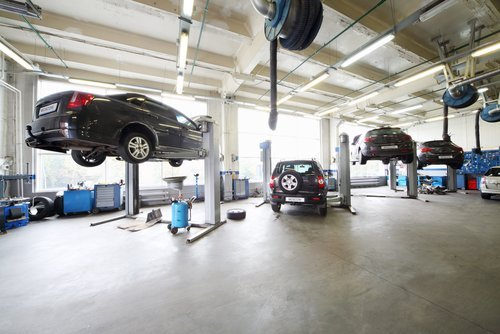 Cars in the service bay of an auto repair shop. | Source: Shutterstock.
