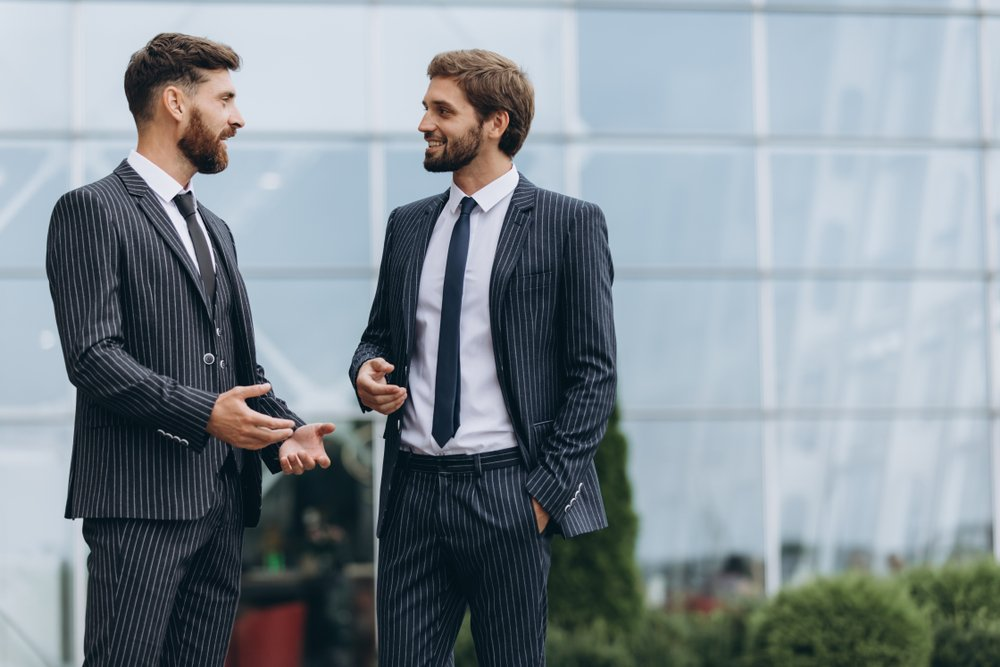 Two young men discussing outside an office building. | Photo: Shutterstock.
