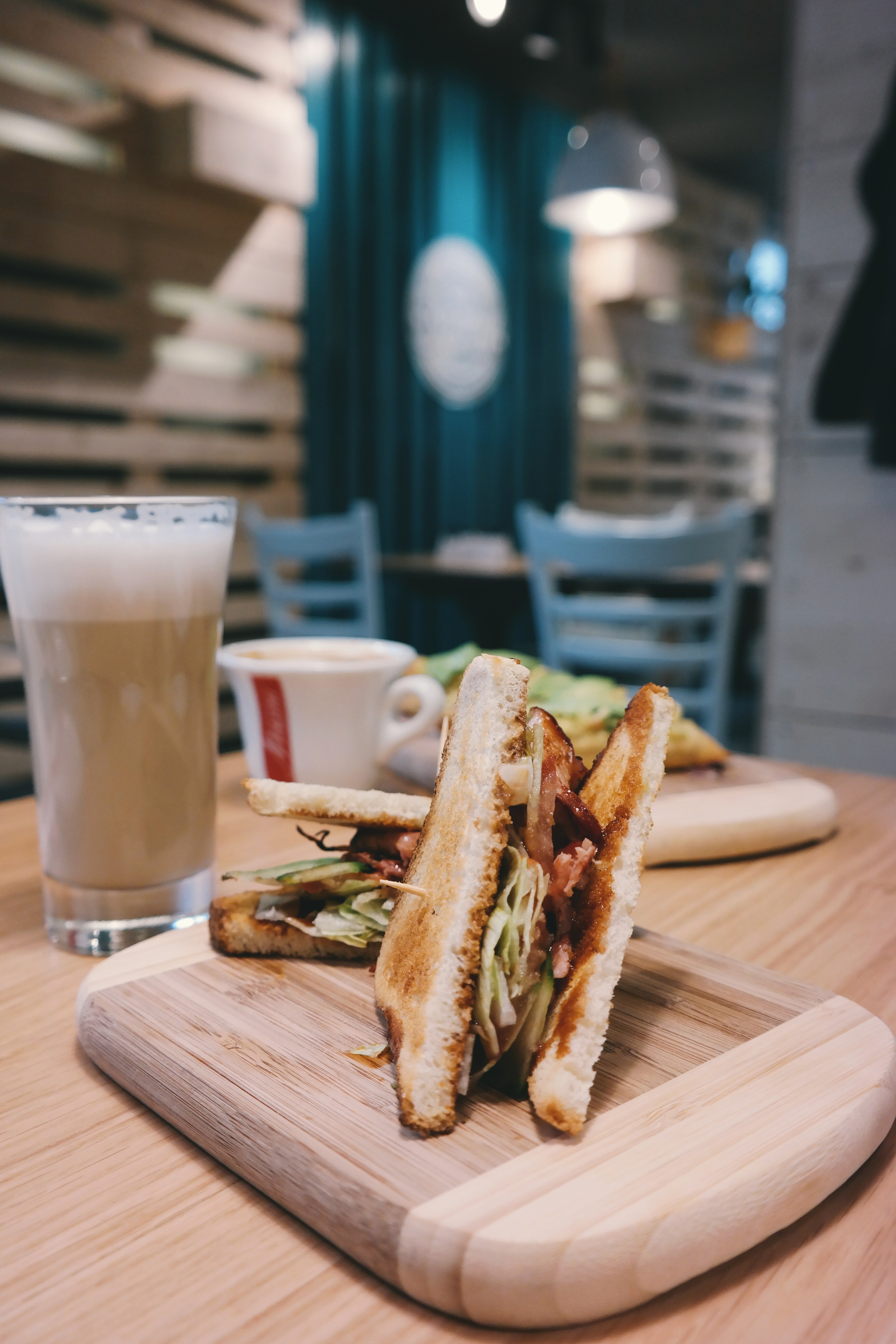 A drink and a couple of sandwiches on a dining table.   Photo: Pexels