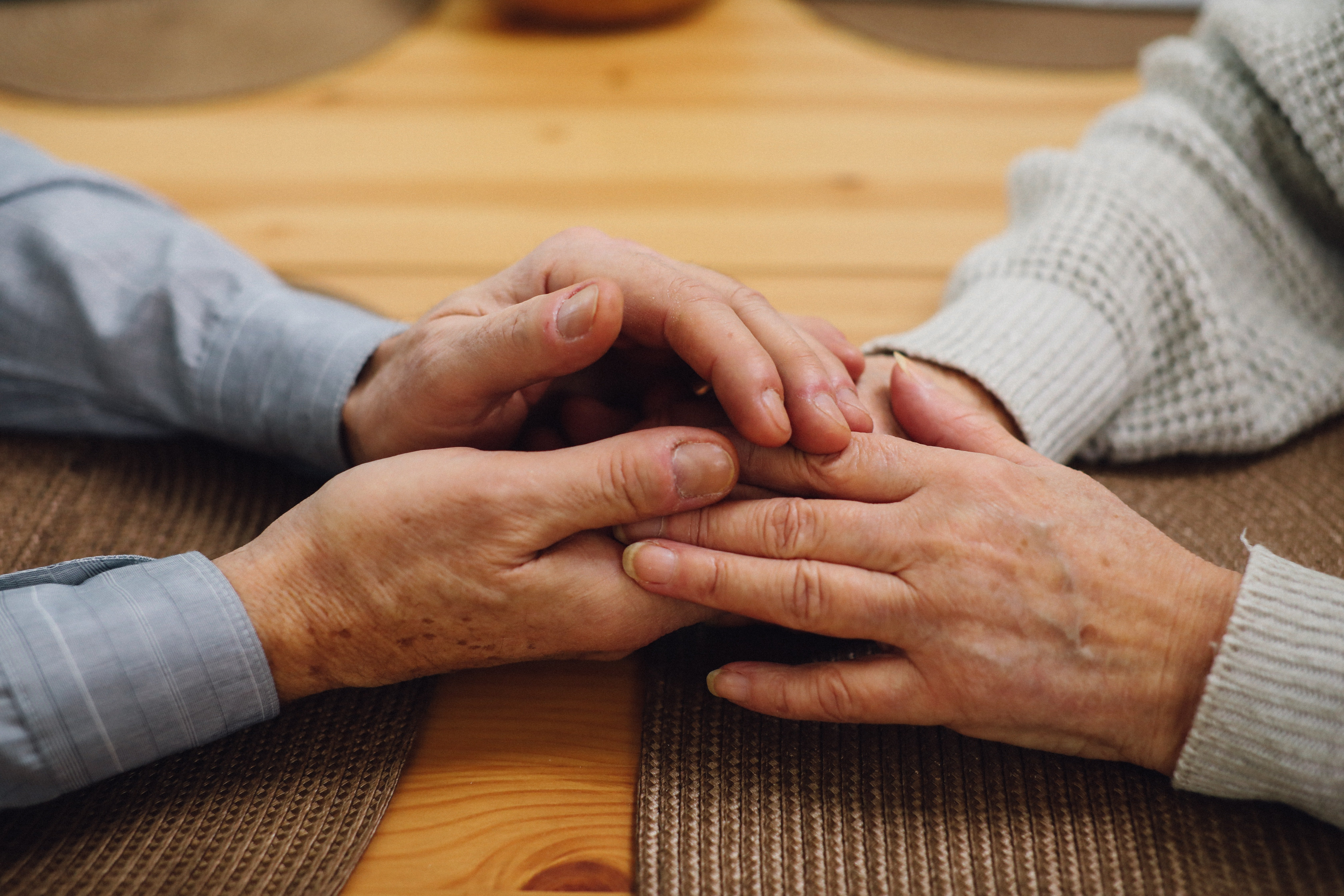 An older couple holding hands across a table.   Source: Pexels/ Tom Leishman