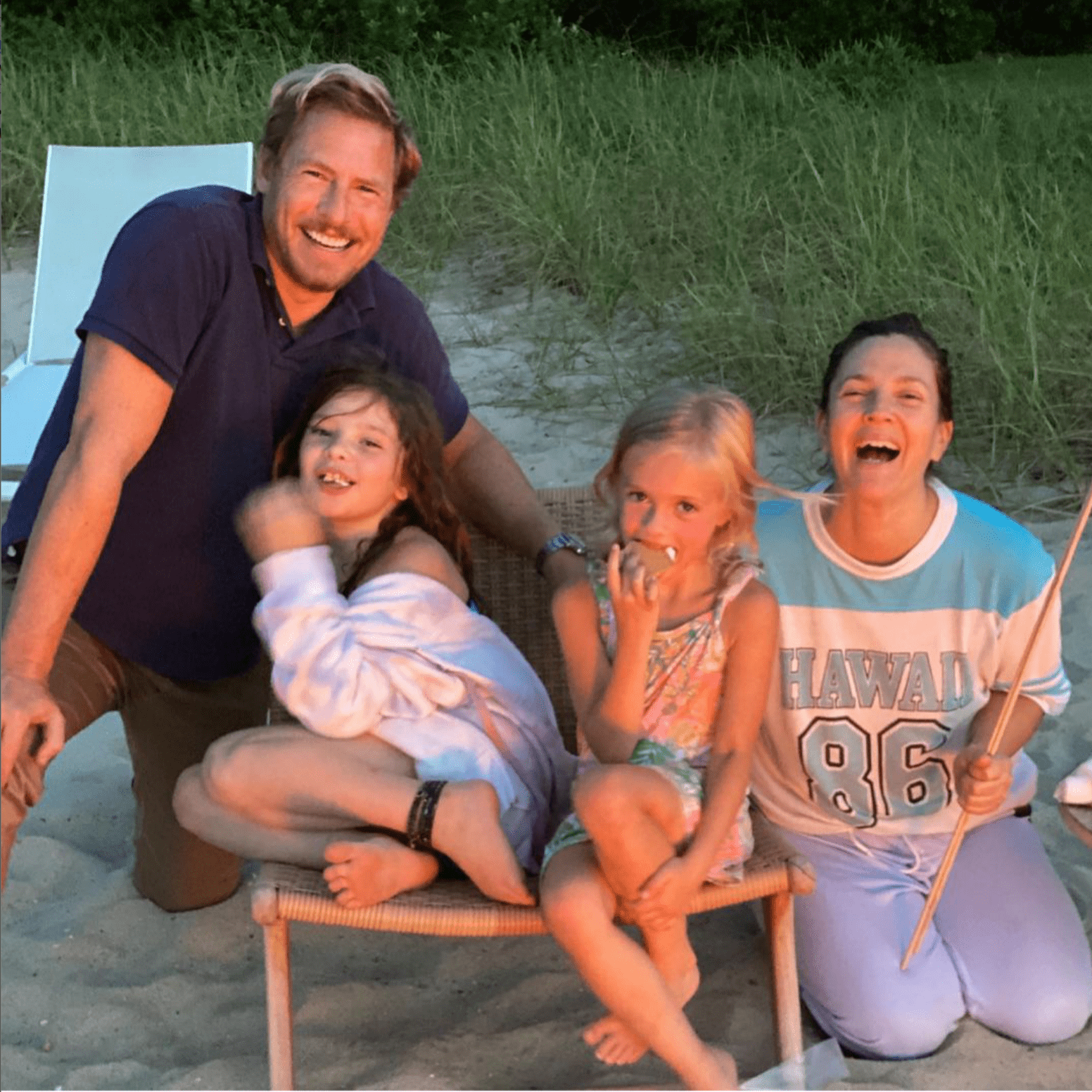 Drew Barrymore, Will Kopelman, Frankie, and Olive huddling together while making s'mores near a fire. | Photo: Instagram/Drew Barrymore