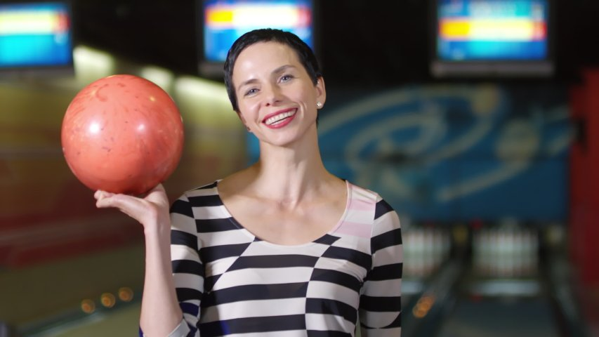 Image of woman holding a bowling ball | Photo: Shutterstock