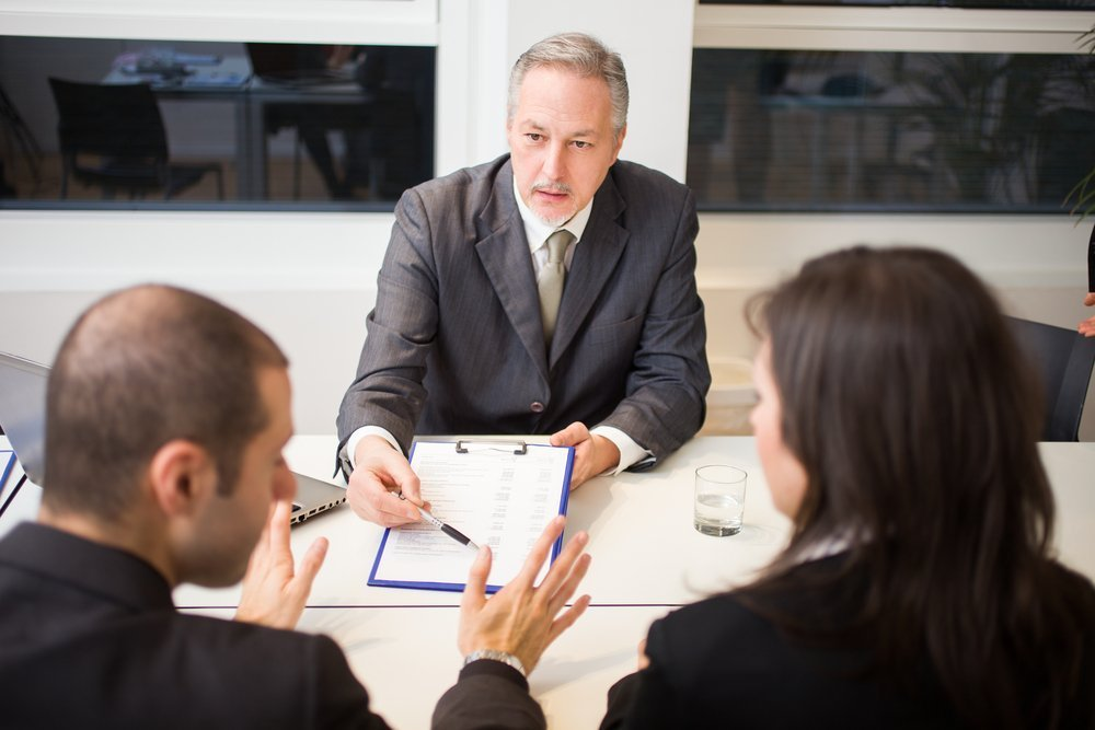 A divorce lawyer attending to a couple in his office. | Photo: Shutterstock