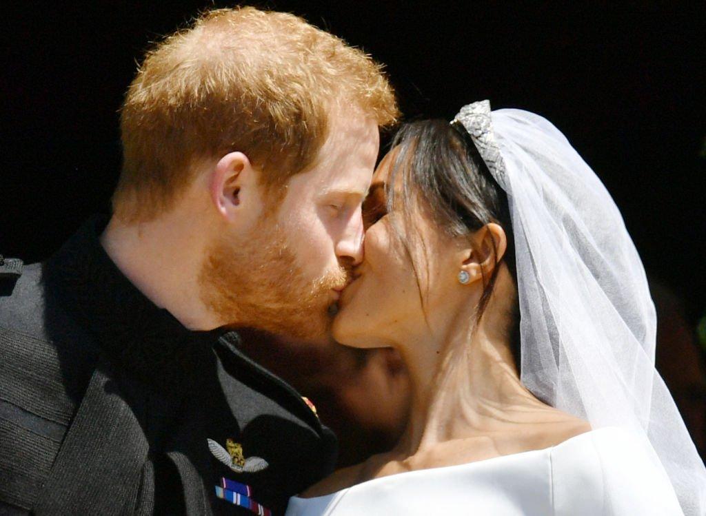 Le Prince Harry et sa femme Meghan Markle, Duchesse de Sussex, s'embrassent. | Getty Images