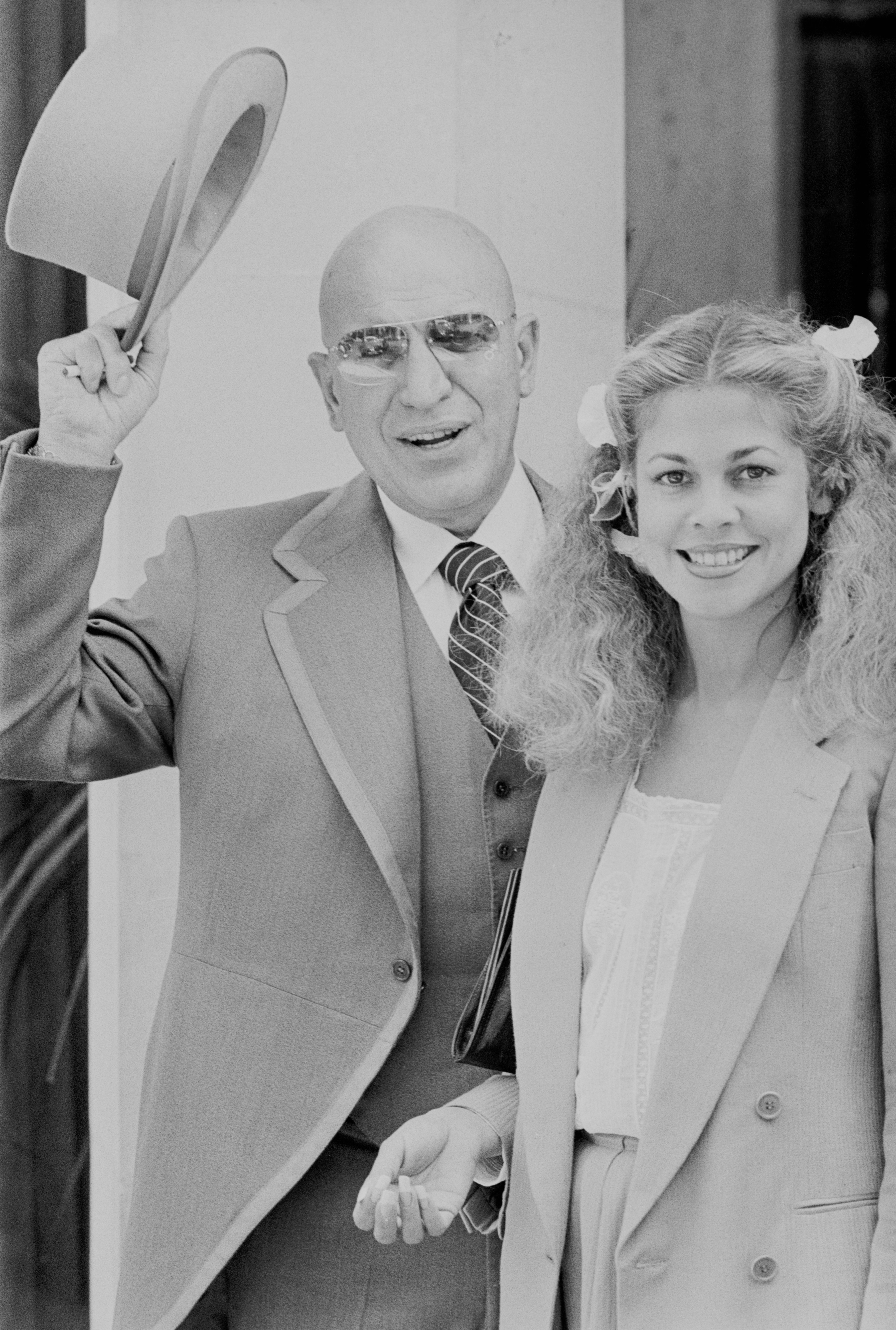 American singer and actor Telly Savalas (1922 - 1994) with girlfriend Sally Adams, UK, 20th June 1977 | Photo: Getty Images