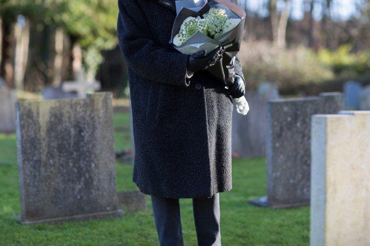 Une personne en deuil tenant un bouquet de fleurs dans un cimetière  Source : Shutterstock