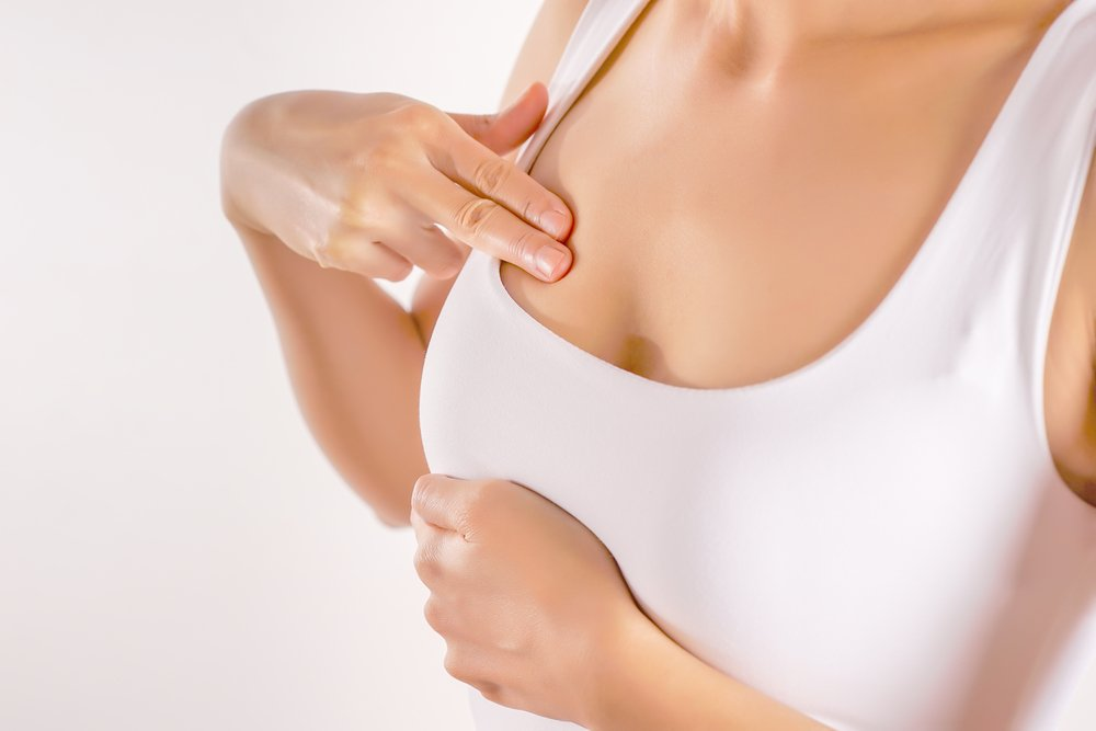 Woman Wearing A White Tank Top Checking Her Breast, Breast Self-Exam (BSE)   Photo: Shutterstock