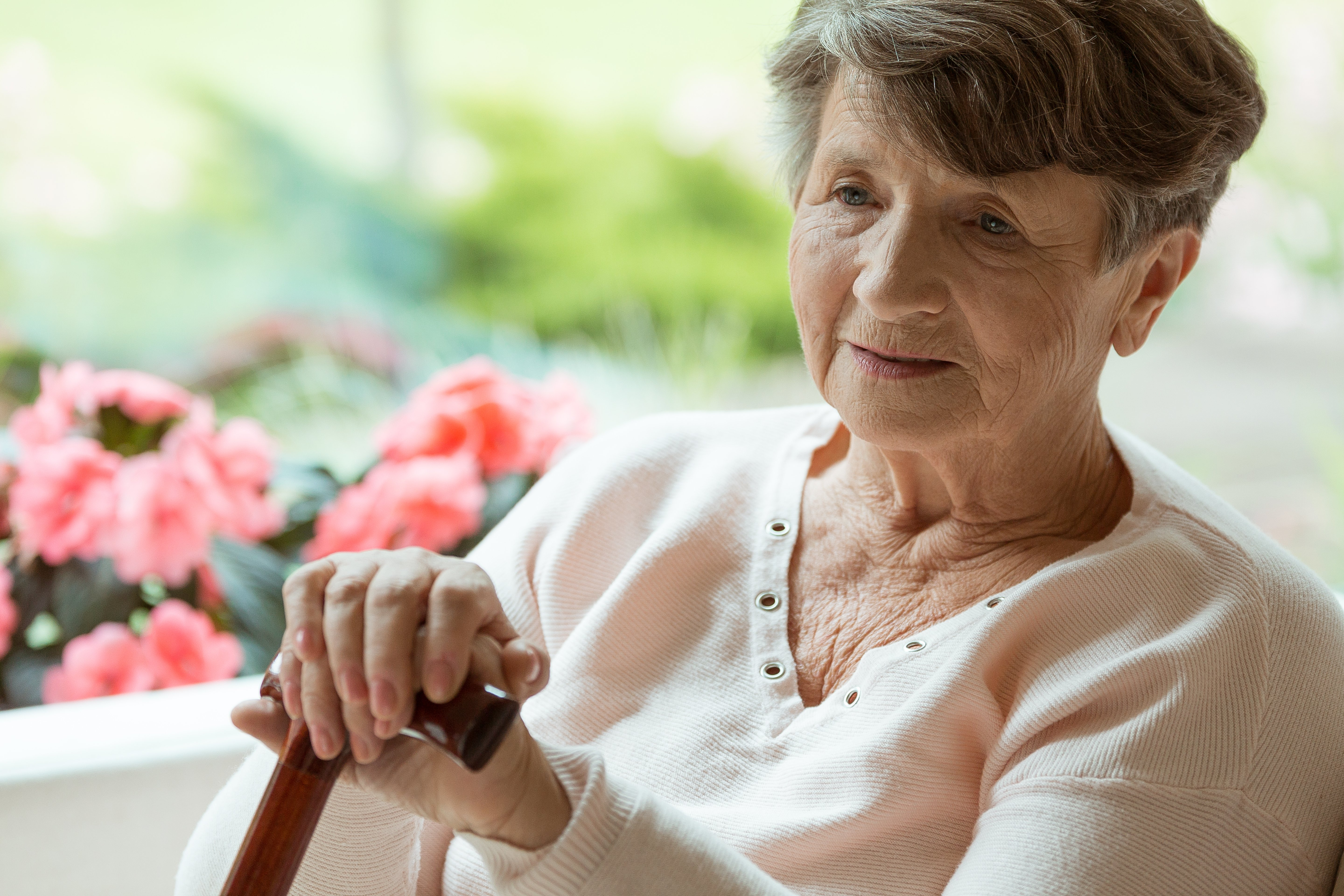 Elder woman sitting on white sofa with walking cane in room with pink flowers | Photo: Shutterstock.com