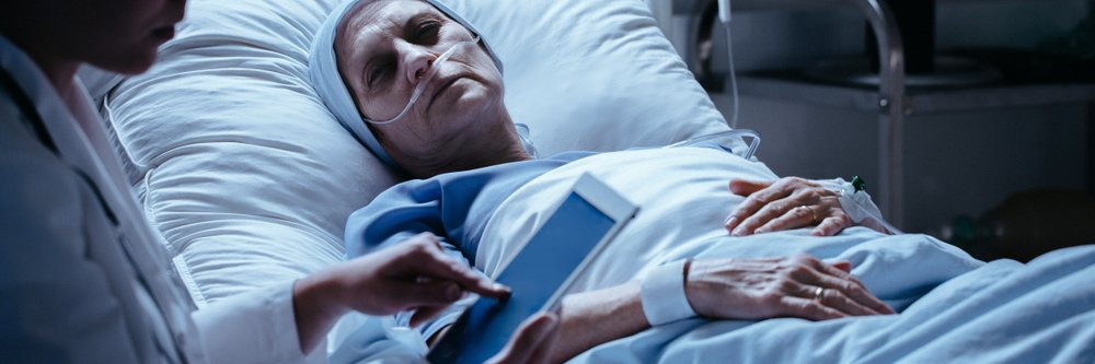 A terminally ill middle-aged woman looking sadly at her doctor. | Photo: Shutterstock