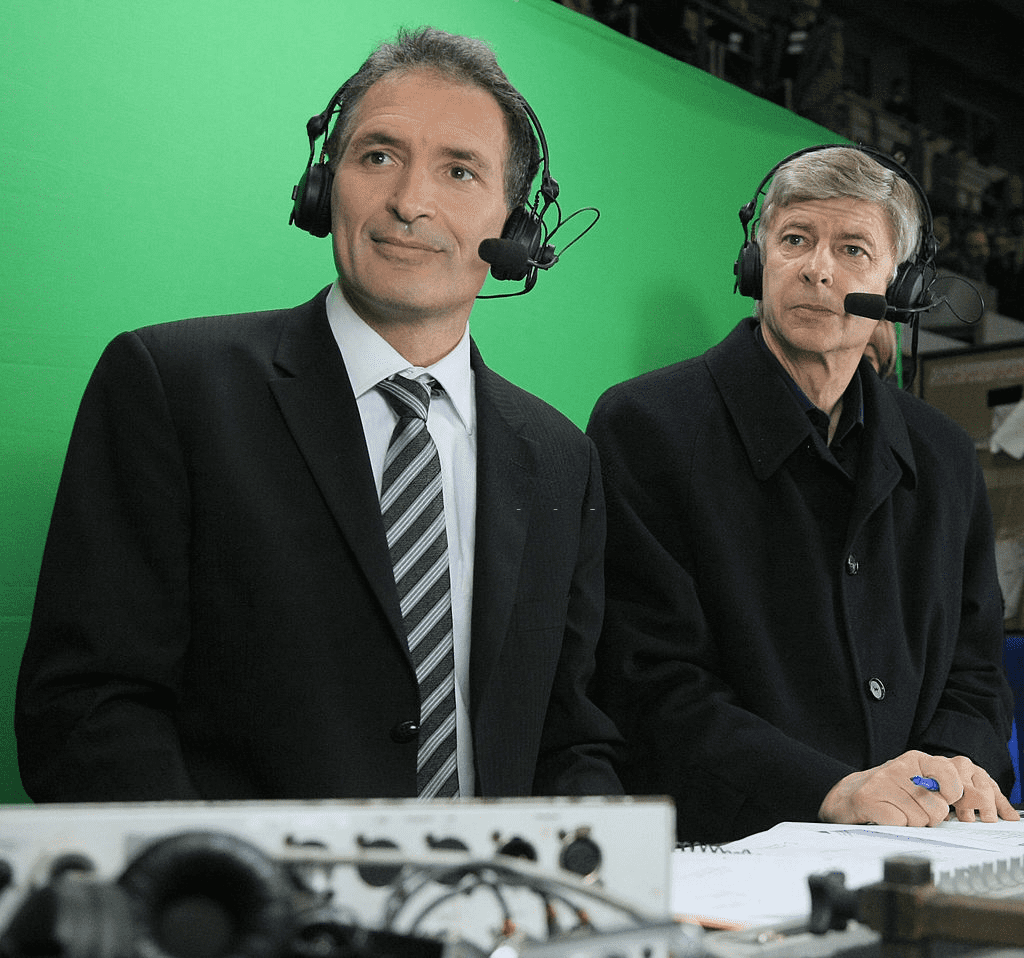 Le journaliste français Christian Jeanpierre et l'entraîneur Arsène Wenger posent dans les tribunes de presse quelques instants avant le début du match amical France-Angleterre du 26 mars 2008 au Stade de France à Saint-Denis, en banlieue parisienne. | Photo : Getty Images