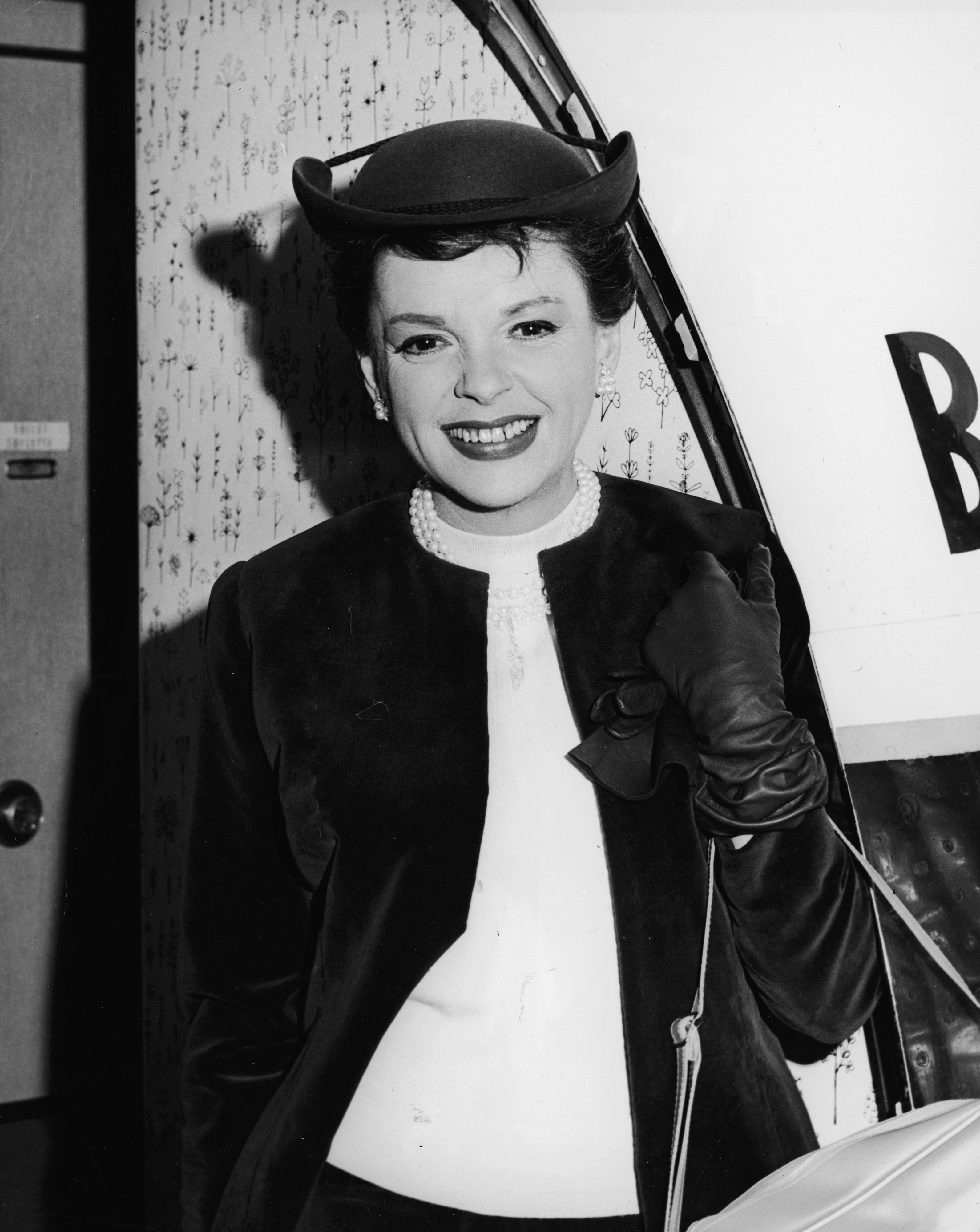 "Judy Garland (1922-1969) smiles and boards a plane en route to London to attend the premiere of her film, ""I Could Go on Singing."" 