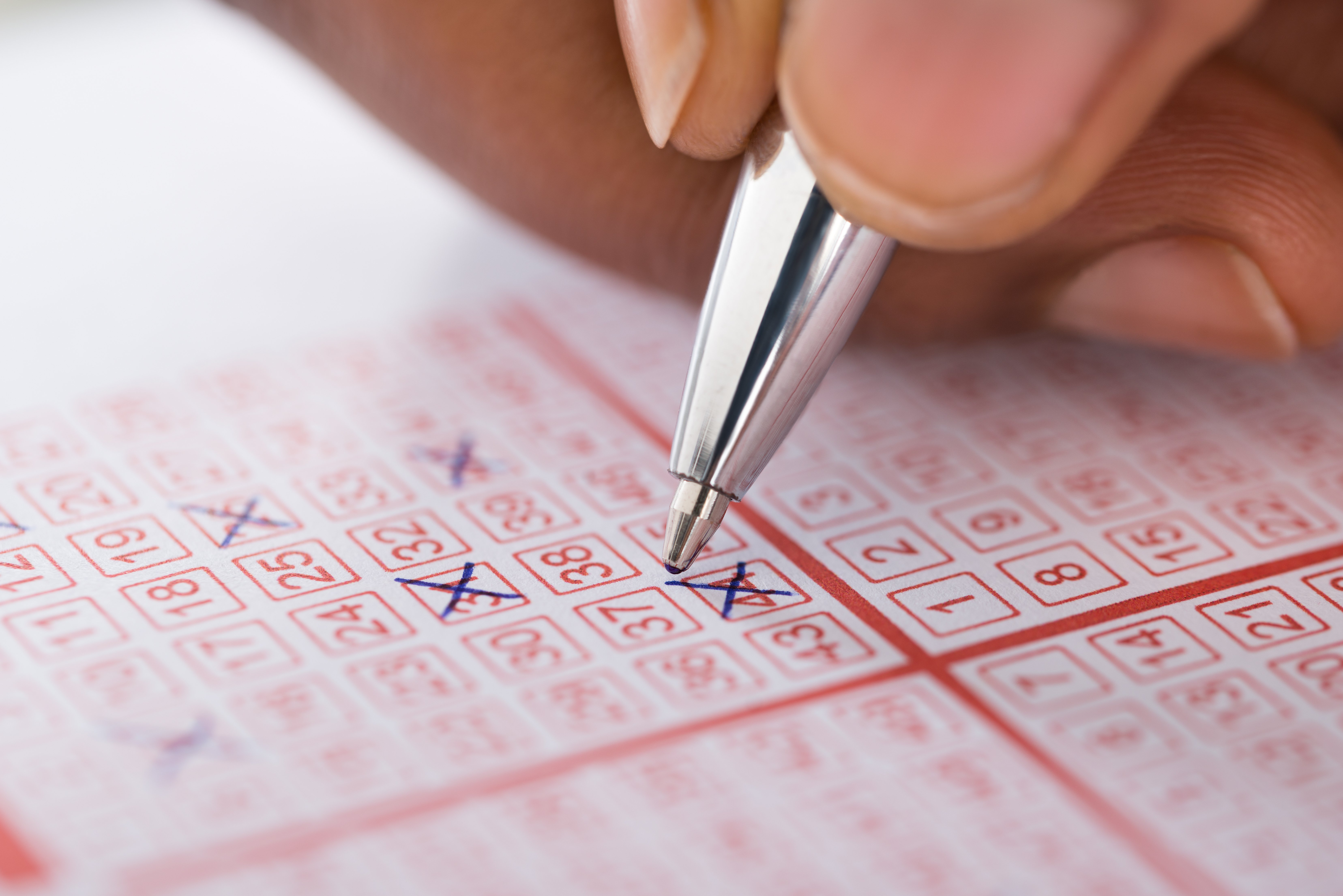 A person choosing their lottery numbers | Photo: Shutterstock