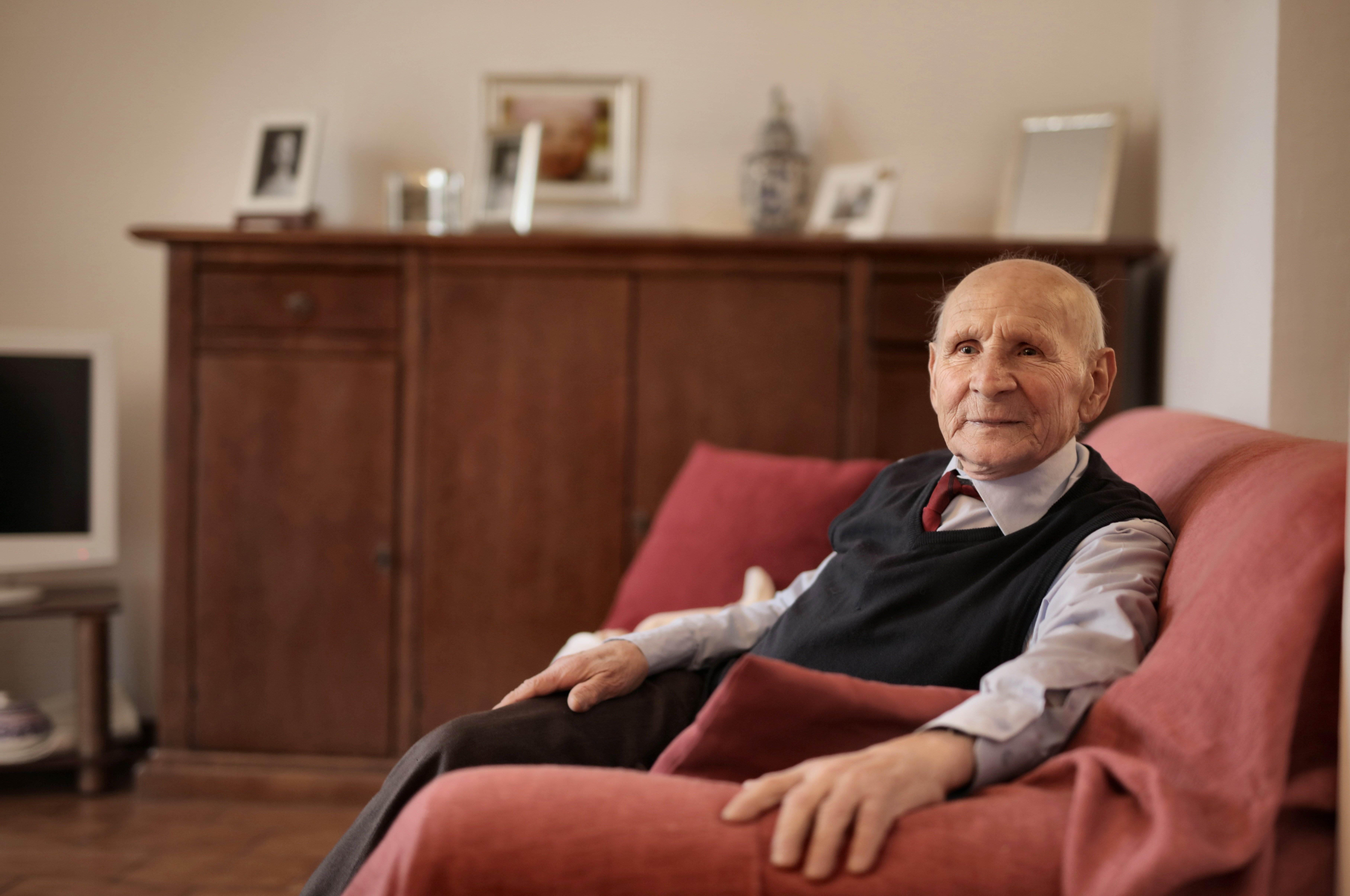 An elderly man sitting on a couch.   Pexels/ Andrea Piacquadio