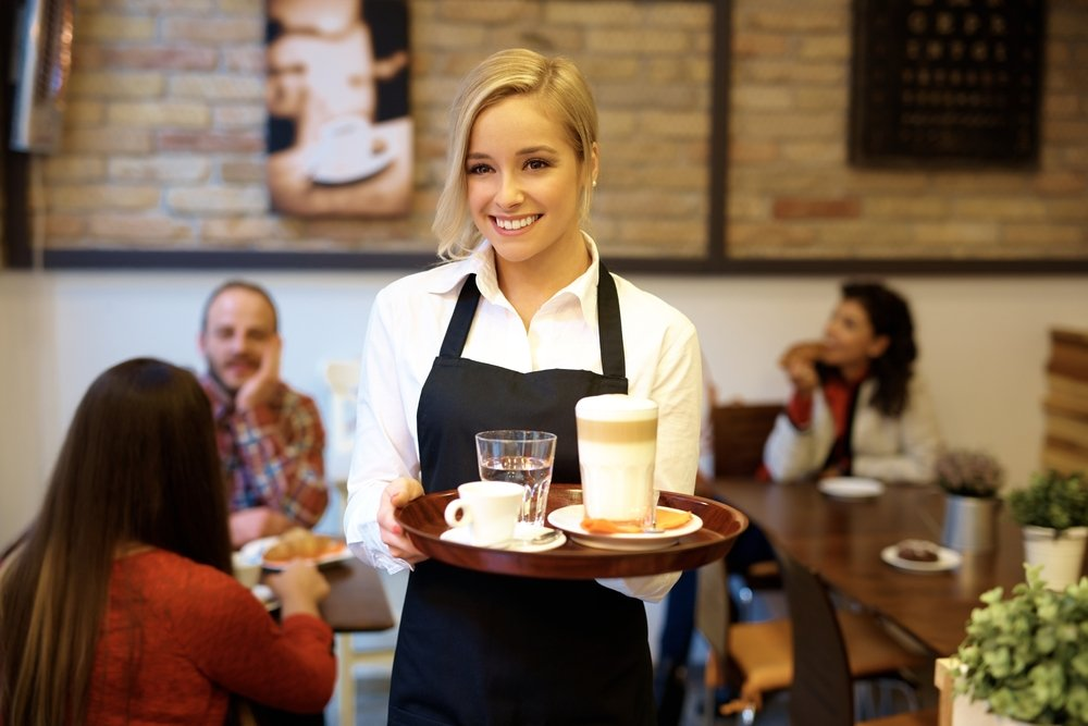 Waitress smiling while holding tray with coffee.|Source: Shutterstock