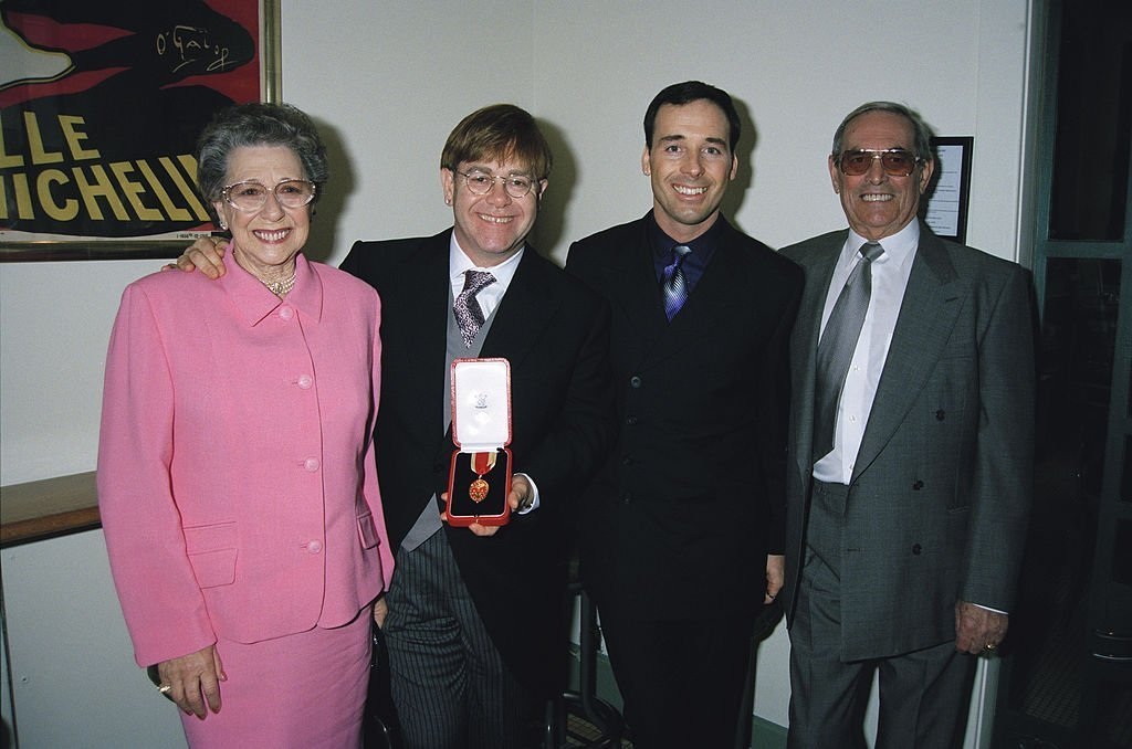 Elton John with his mother Sheila Farebrother, his stepfather and his partner David Furnish, after receiving his knighthood. | Source: Getty Images