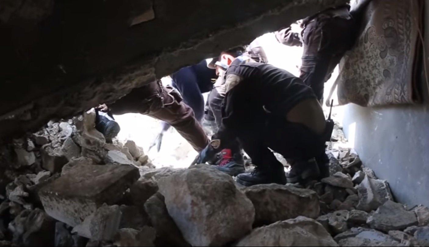 Rescatistas raspando la roca desmenuzada para revelar la cabeza de un pequeño cachorro. Fuente: YouTube / Daily Mail