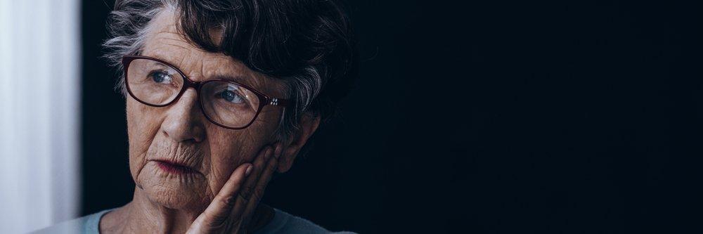Une vieille dame seule, atteinte de la maladie d'Alzheimer, qui regarde par la fenêtre. | Source : Shutterstock