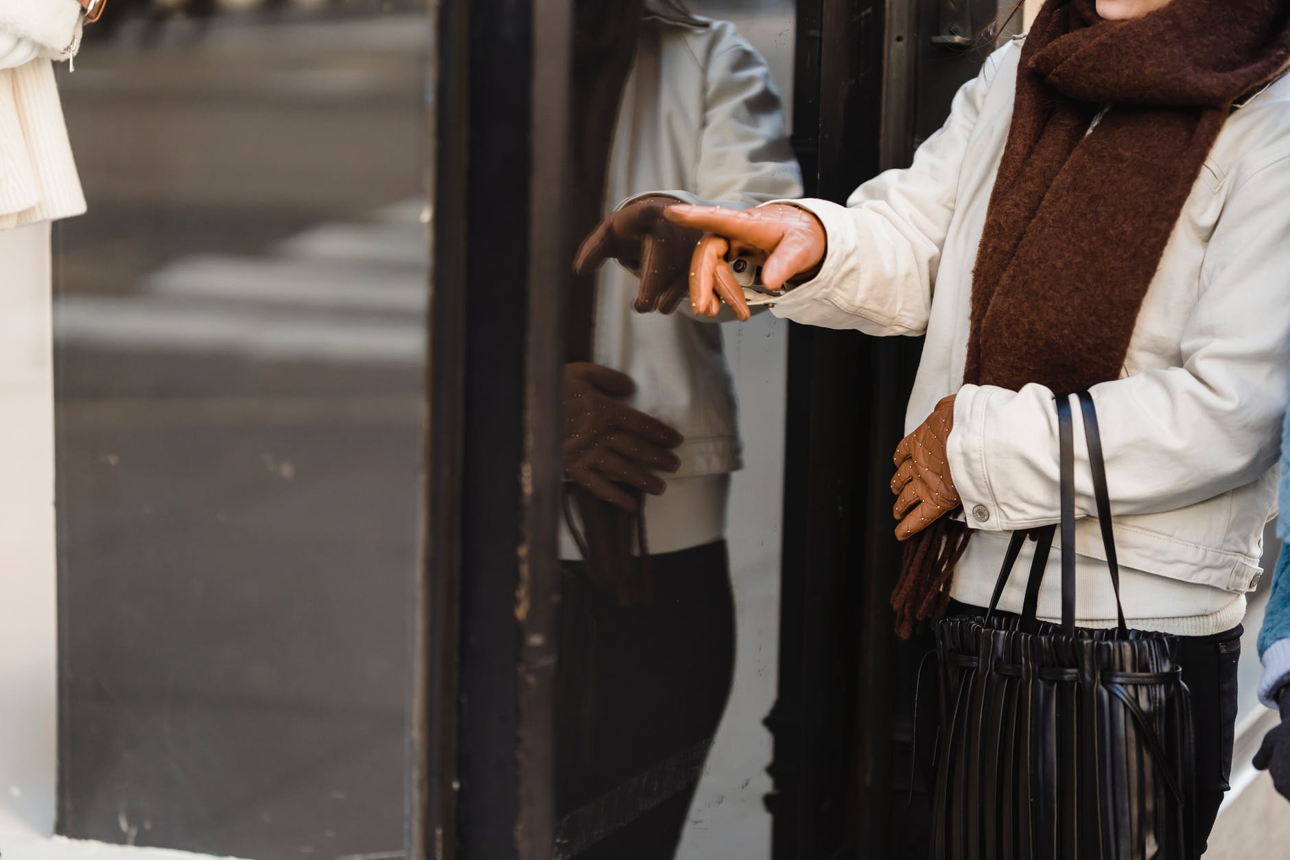 Woman with gloves pointing at storefront | Source: Pexels