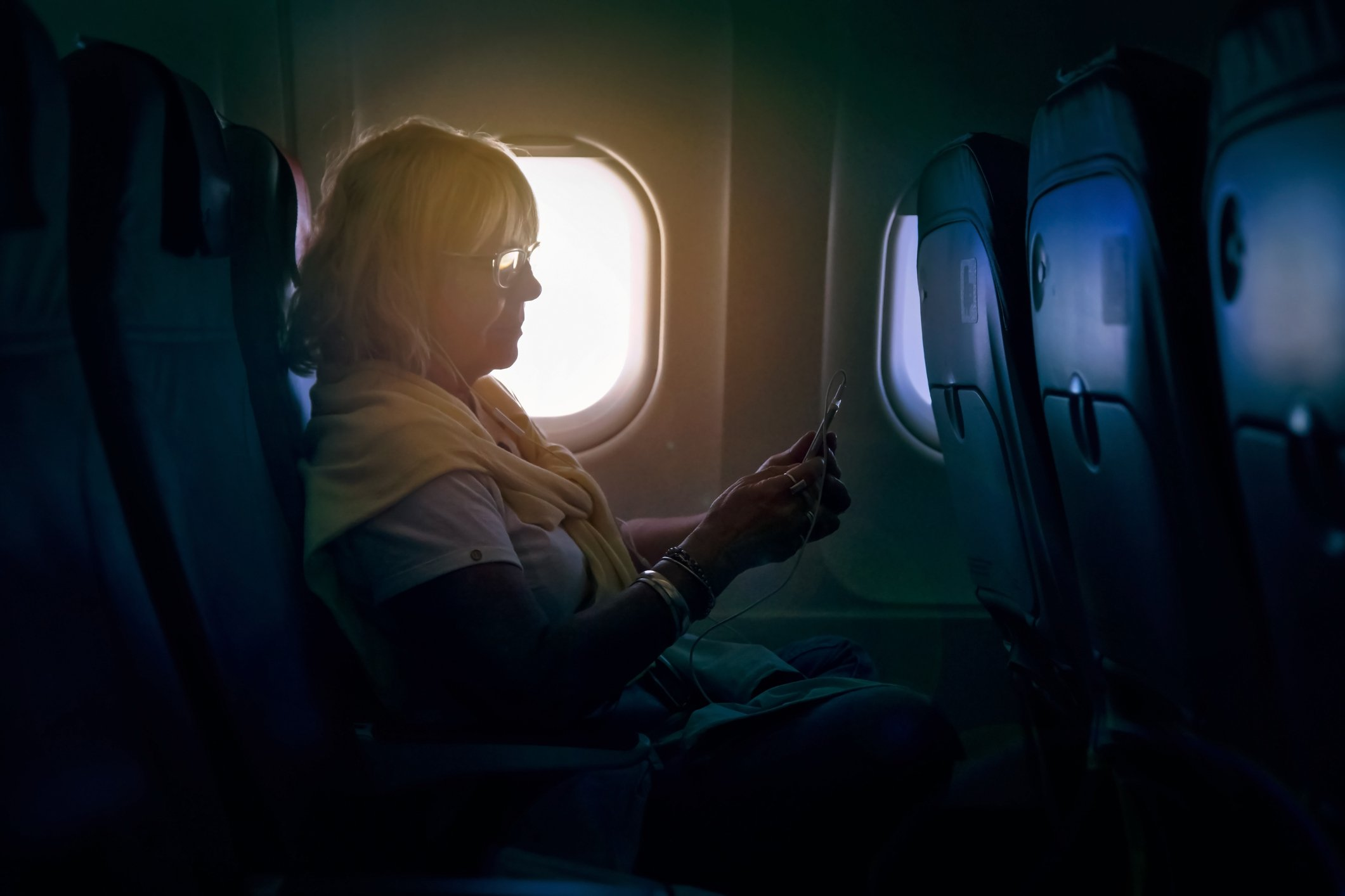 Senior woman using a smartphone on a plane | Photo: Getty Images